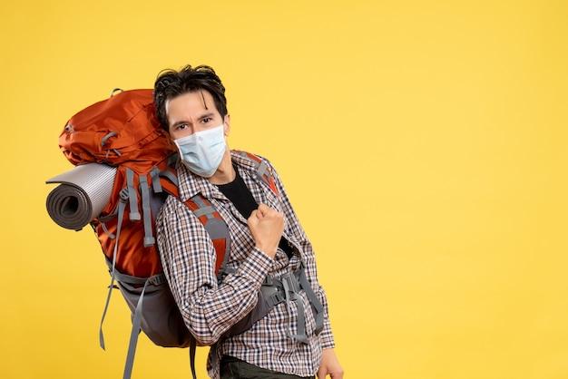 Vooraanzicht jong mannetje dat voor wandelen in masker op geel voorbereidingen treft