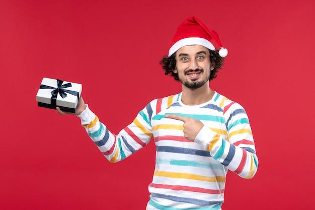 Vooraanzicht jong mannetje dat weinig aanwezig op rode muur houdt emoties vakantie nieuwjaar