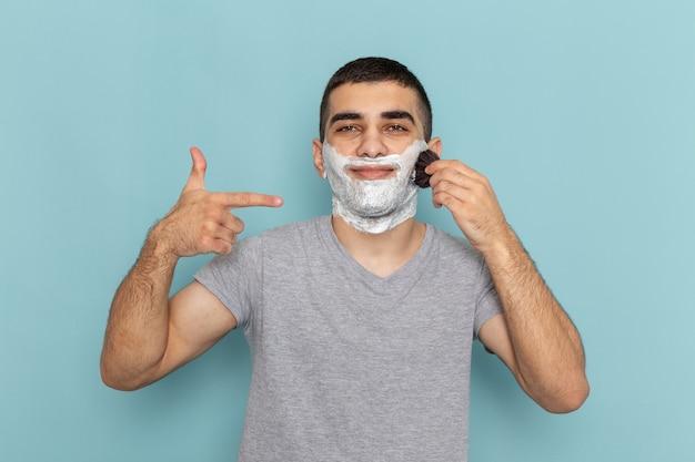 Vooraanzicht jong mannetje in grijs t-shirt met wit schuim op zijn gezicht dat het met borstel op het ijsblauw wrijft