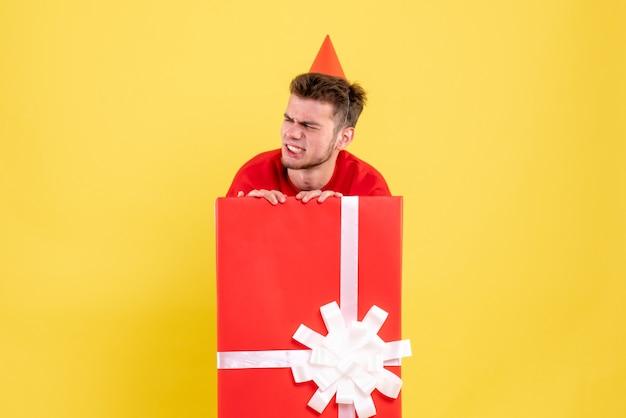 Vooraanzicht jong mannetje in rood overhemd in huidige doos