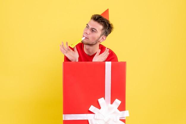 Vooraanzicht jong mannetje in rood overhemdszitting in huidige doos