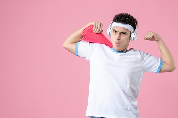 Vooraanzicht jong mannetje in sportkleren met yogamat en hoofdtelefoons op roze muur