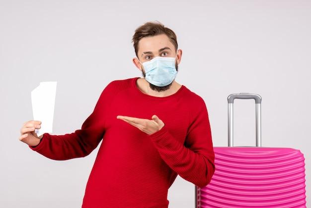 Vooraanzicht jong mannetje in steriel masker met kaartjes op witte muur reis covid-vlucht reis vakantie virus kleur emotie