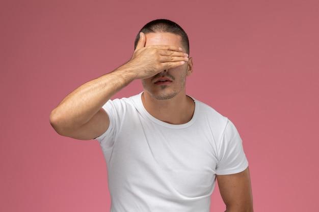 Vooraanzicht jong mannetje in wit overhemd beklemtoond die zijn gezicht op roze achtergrond bedekken