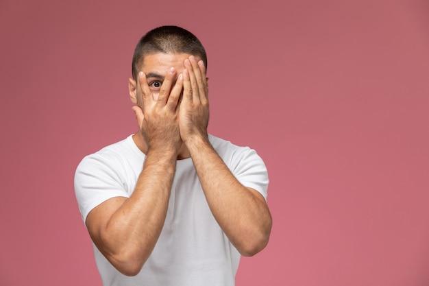Vooraanzicht jong mannetje in wit overhemd dat zijn gezicht op roze achtergrond behandelt