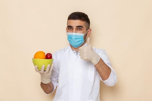 Vooraanzicht jong mannetje in wit pak dat masker en handschoenen draagt die plaat met vruchten op beige houden