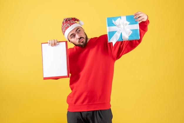 Vooraanzicht jong mannetje met aanwezige kerstmis en nota over gele achtergrond