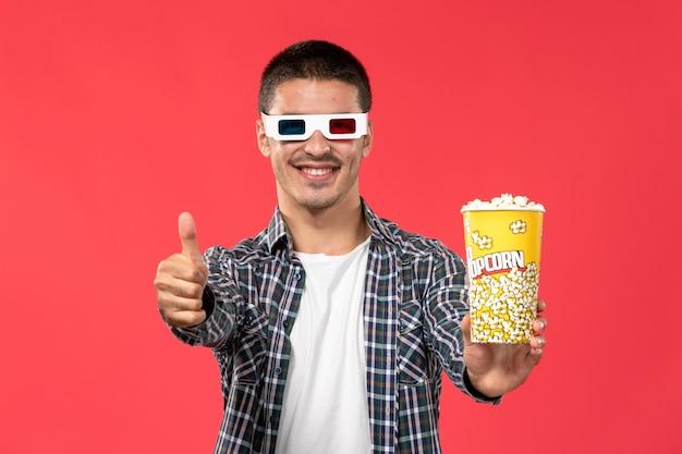 Vooraanzicht jong mannetje met popcornpakket in d zonnebril op lichtrode muur mannelijke bioscoop bioscoop film leuke tijden