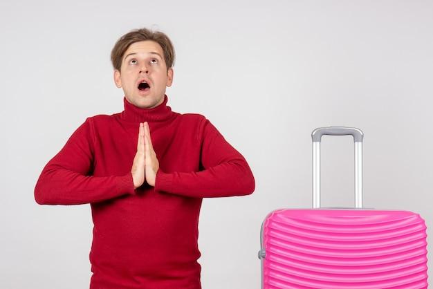 Vooraanzicht jong mannetje met roze zak die op witte achtergrond bidt