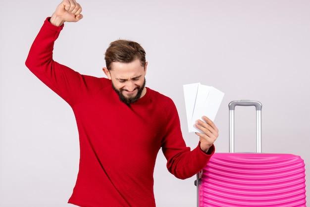 Vooraanzicht jong mannetje met roze zak en bedrijf vliegtickets die zich op witte muur verheugen reis vlucht reis toeristische vakantie emotie foto