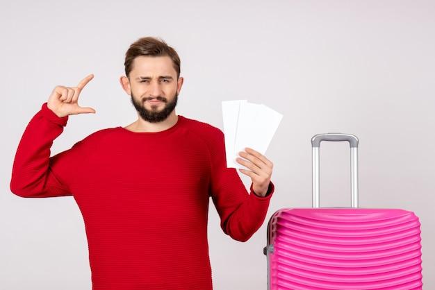 Vooraanzicht jong mannetje met roze zak en kaartjes houden op witte muur kleuren reis vakantie vlucht reis toerist