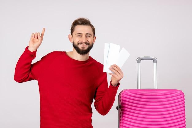 Vooraanzicht jong mannetje met roze zak en kaartjes houden op witte muur reis vakantie vlucht reis zomertoerist