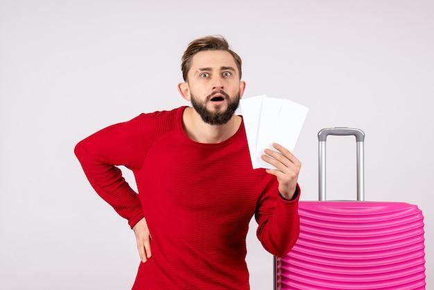 Vooraanzicht jong mannetje met roze zak en vliegtuigtickets op witte muur te houden reis vlucht reis vakantie emoties foto toerist