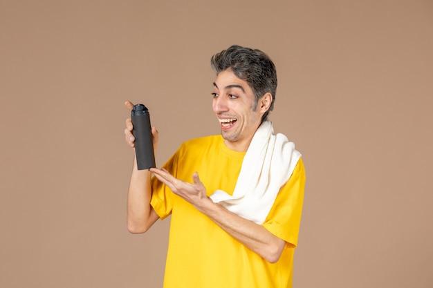 Vooraanzicht jong mannetje met schuim en handdoek die zich voorbereiden om zijn gezicht op roze achtergrond te scheren