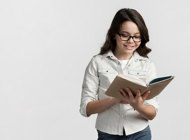 Vooraanzicht jong meisje dat een boek leest