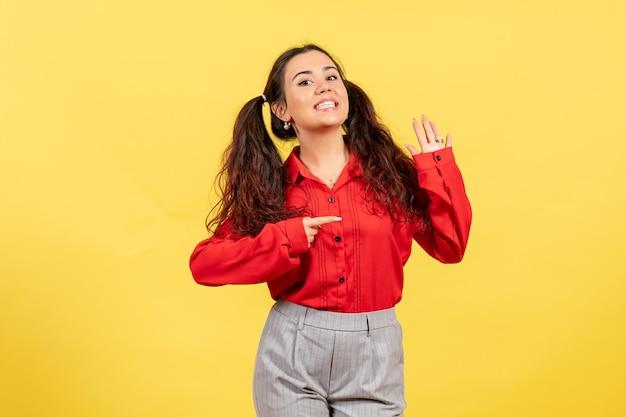 Vooraanzicht jong meisje in rode blouse met lachend gezicht op gele achtergrondkleuren onschuld kind jeugd kind meisje