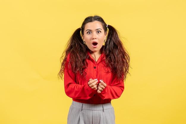 Vooraanzicht jong meisje in rode blouse met schattig haar en geschokt gezicht op gele achtergrond kind kind meisje jeugd onschuld kleur