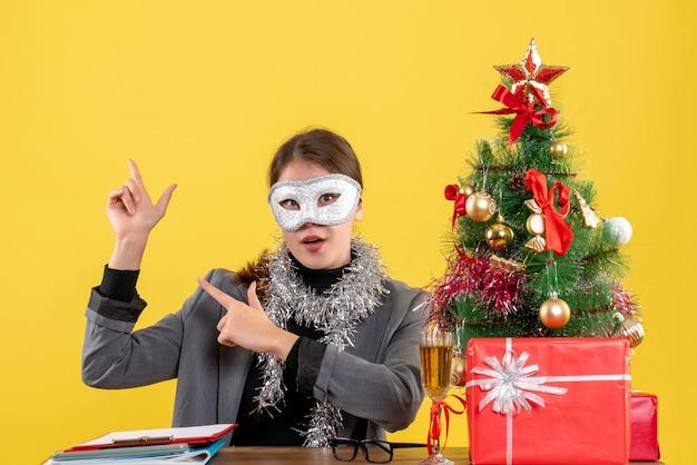 Vooraanzicht jong meisje met masker zittend aan de tafel wijzend met vinger iets kerstboom en geschenken cocktail