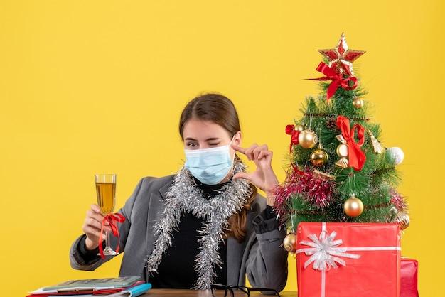 Vooraanzicht jong meisje met medisch masker zittend aan de tafel knipperend oog voorstelt een toast kerstboom en geschenken cocktail