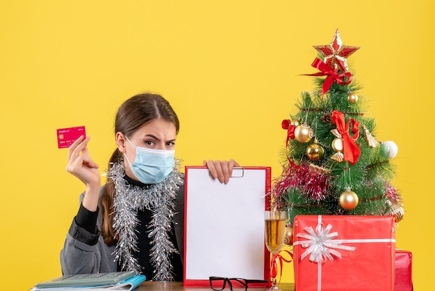 Vooraanzicht jong meisje met medische masker zittend aan de tafel met creditcard kerstboom en geschenken cocktail