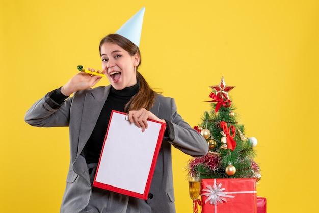 Vooraanzicht jong meisje met partij glb bedrijf noisemaker en documenten staan in de buurt van kerstboom en geschenken cocktail