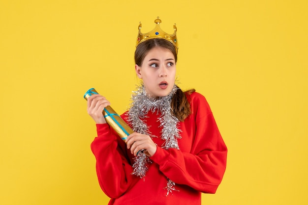 Vooraanzicht jong meisje met rode sweater en de partijpopper van de kroonholding