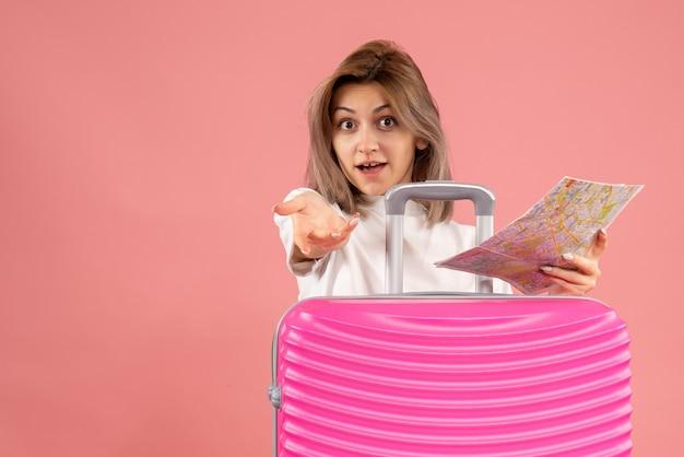 Vooraanzicht jong meisje met roze koffer met kaart die hand reikt