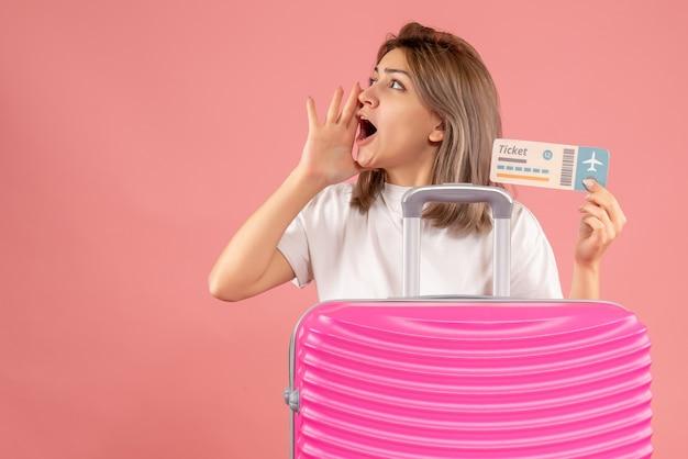 Vooraanzicht jong meisje met roze koffer met kaartje dat iemand belt