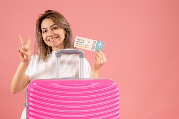 Vooraanzicht jong meisje met roze koffer met kaartje dat overwinningsteken maakt