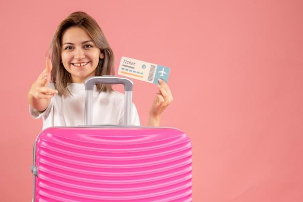 Vooraanzicht jong meisje met roze koffer met kaartje dat vingerpistool naar voren zet