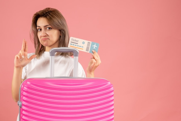 Vooraanzicht jong meisje met roze koffer met kaartje dat vingerpistool teken maakt