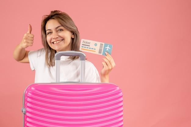 Vooraanzicht jong meisje met roze koffer met kaartje met duimen omhoog