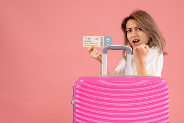 Vooraanzicht jong meisje met roze koffer met ticket