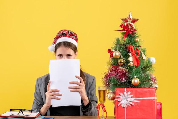 Vooraanzicht jong meisje met xmas hoed zittend aan de tafel die haar gezicht bedekt met documenten kerstboom en geschenken cocktail