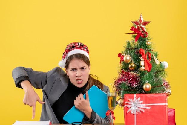 Vooraanzicht jong meisje met xmas hoed zittend aan tafel acteren met woede kerstboom en geschenken cocktail