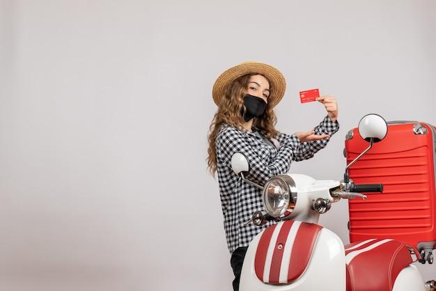 Vooraanzicht jong meisje met zwart masker dat kaartje omhoog houdt dat dichtbij rode bromfiets staat