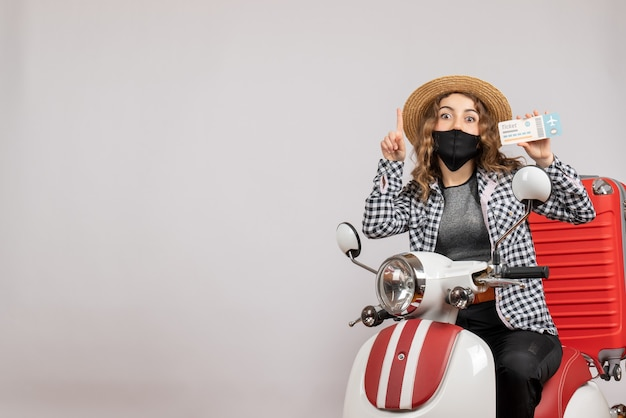Vooraanzicht jong meisje op bromfiets met koffer met ticket