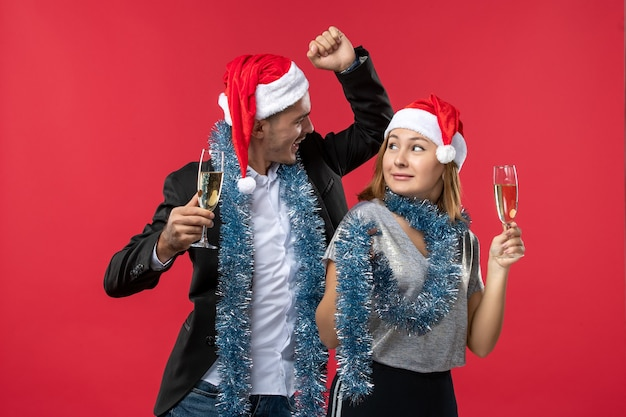 Vooraanzicht jong paar die nieuw jaar op een rode kerstmisliefde van de bureaupartij vieren