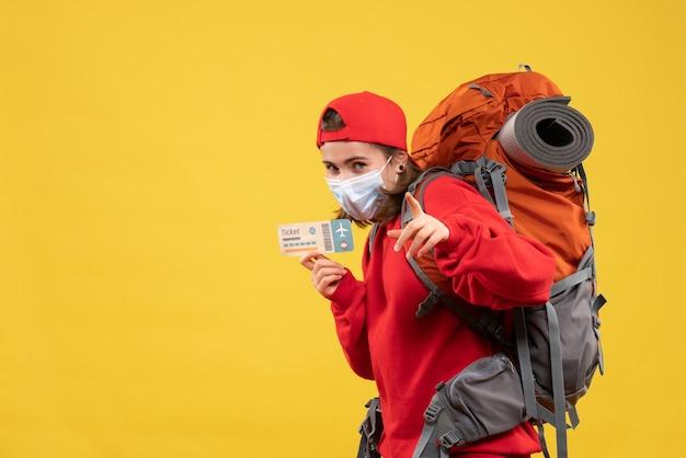 Vooraanzicht jong reizigersmeisje met rugzak en het vliegticket van de maskerholding die op camera richten