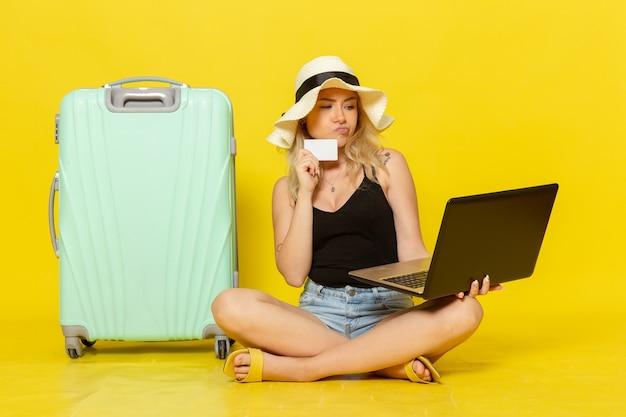 Vooraanzicht jong wijfje dat haar laptop en witte kaart houdt