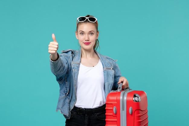 Vooraanzicht jong wijfje dat haar rode zak houdt en voor reis op lichtblauwe ruimte voorbereidingen treft