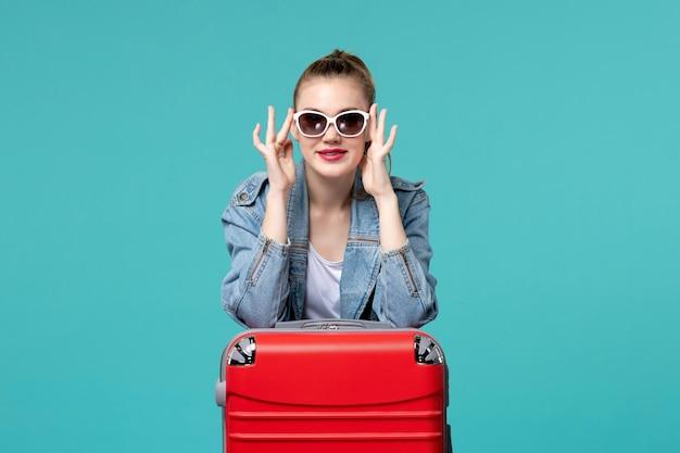 Vooraanzicht jong wijfje dat haar zonnebril draagt en voor vakantie op blauwe ruimte voorbereidingen treft