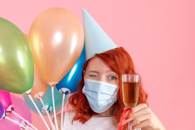 Vooraanzicht jong wijfje dat kleurrijke ballons en glas champagne op roze houdt