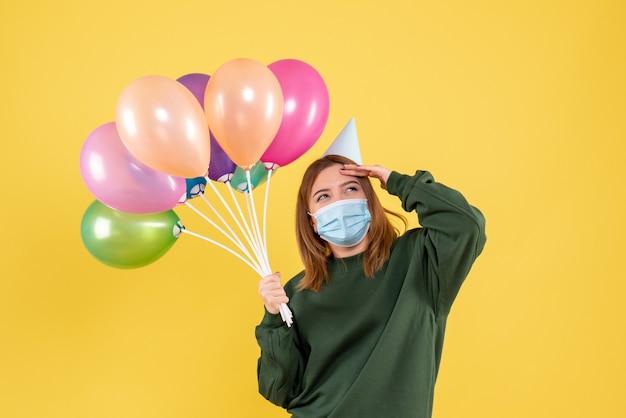 Vooraanzicht jong wijfje dat kleurrijke ballons houdt