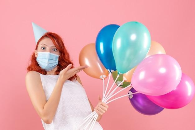 Vooraanzicht jong wijfje dat kleurrijke ballons in masker op roze houdt