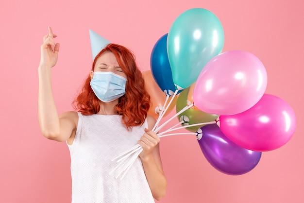 Vooraanzicht jong wijfje dat kleurrijke ballons in masker op roze partij van de het virus covid-xmas van de bureaukleur houdt