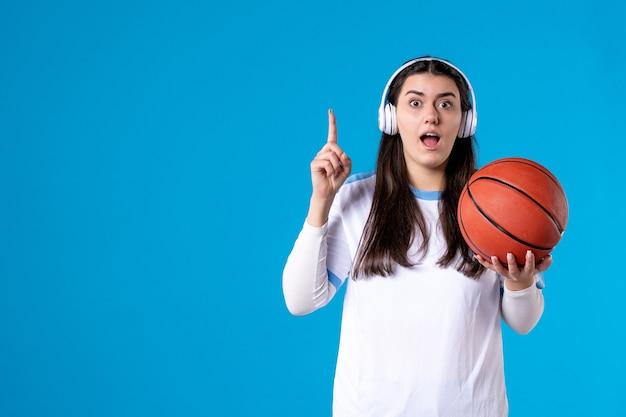 Vooraanzicht jong wijfje dat met oortelefoons basketbal op blauwe muur houdt