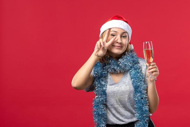 Vooraanzicht jong wijfje dat nieuwe jaren viert die op kerstmisvakantie van de rode muurkleur komen
