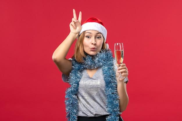 Vooraanzicht jong wijfje dat nieuwe jaren viert die op rode kerstmisvakantie van de bureaukleur komen