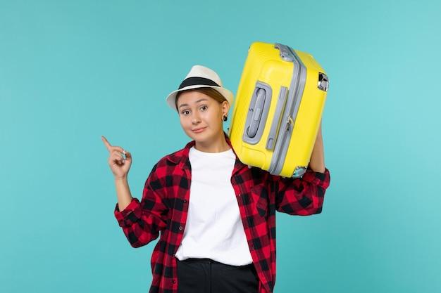 Vooraanzicht jong wijfje dat op vakantie gaat met haar grote zak op de blauwe ruimte